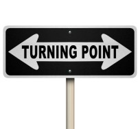 A road sign with the words Turning Point and arrows pointing lef