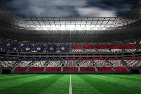 Digitally generated american national flag against large football stadium