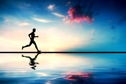 Silhouette of man running at sunset. Water reflection