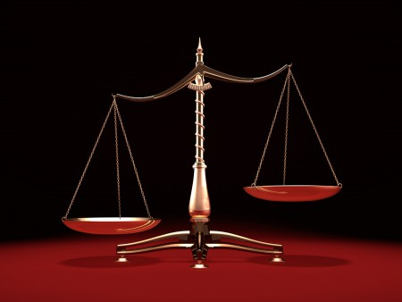 Biased brass weight scales Law and Justice symbol Isolated on bl