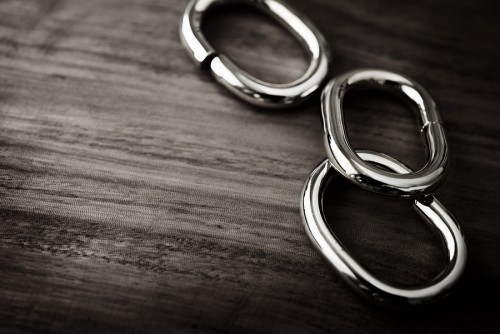 Shiny Chrome or silver chain links on a grungy wooden table. sha
